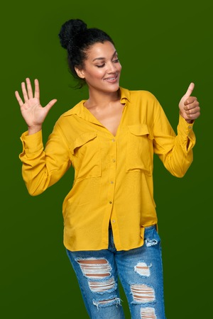 number six: Hand counting - six fingers. Happy mixed race african american - caucasian woman indicating the number six with her fingers Stock Photo