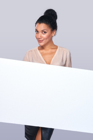 advertising space: Smiling business woman showing blank whiteboard with copy space for advertising text, over grey background Stock Photo