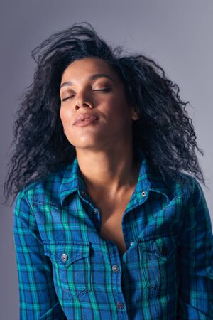 Portrait of mixed race african american - caucasian woman relaxing with closed eyes throwing back Imagens