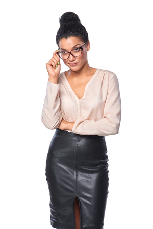 dubious: Young business woman looking skeptically over her spectacles, over white background