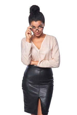 hesitations: Young business woman looking skeptically over her spectacles, over white background