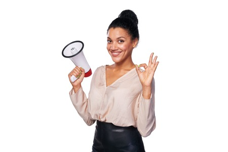 job advertisement: Business, communication, information concept. Confident smiling mixed race caucasian - african american business woman holding loudspeaker and gesturing OK hand sign Stock Photo