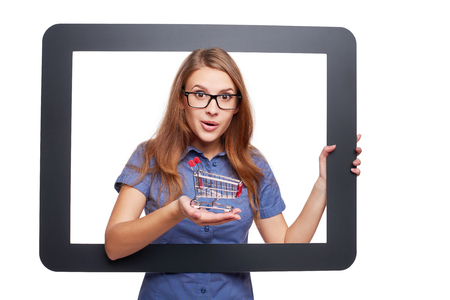 looking through frame: Online shopping concept. Surprised female peeping out of tablet frame and shwoing a small empty shopping cart, over white background