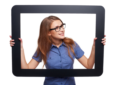 looking through frame: Woman peeping out of tablet frame, over white background Stock Photo