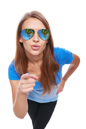 woman pointing: Holidays, travel, vacation concept. Woman in sunglasses with tropical resort palm trees reflection pointing her finger at camera and asking you