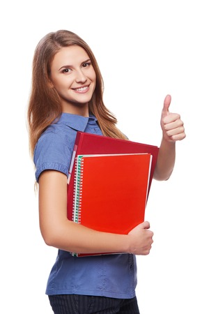 great job: Young woman holding textbooks smiling at camera and gesturing thumb up, over white background Stock Photo