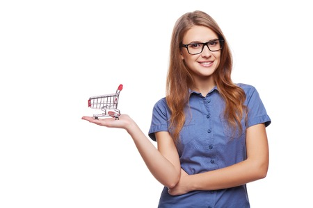 woman shopping cart: Shopping concept. Portrait of smiling woman holding small empty shopping cart on her palm, isolated on white background