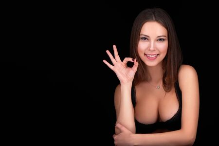 nude model: Beauty woman portrait posing in black bra showing her ample cleavage and gesturing OK sign, over black background Stock Photo