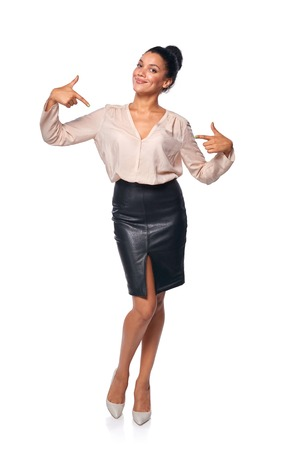 Smiling content business woman in full length pointing at herself, isolated on white background