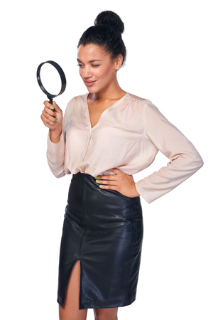 looking through: Search concept. Confident business woman looking through magnifying glass at blank copy space, isolated over white