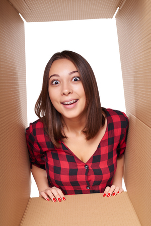 looking through an object: Delivery, relocation and unpacking concept. Smiling happy young girl opening a carton box and looking inside