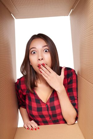 package: Delivery, relocation and unpacking concept. Surprised ovejoyed young girl opening a carton box and looking inside covering her mouth with a hand Stock Photo