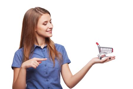 cart: Shopping concept. Portrait of smiling woman holding small empty shopping cart on her palm and pointing at it, isolated on white background Stock Photo