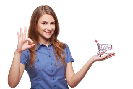 hand basket: Shopping concept. Portrait of smiling woman holding small empty shopping cart on her palm and gesturing OK sign, isolated on white background