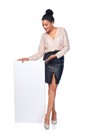 presenting: Business woman standing with blank white banner in full length presenting advertising your product, over white background