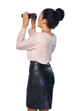 Business search concept. Back view of smiling happy business woman looking through binoculars at blank copy space, isolated over white Stock Photo