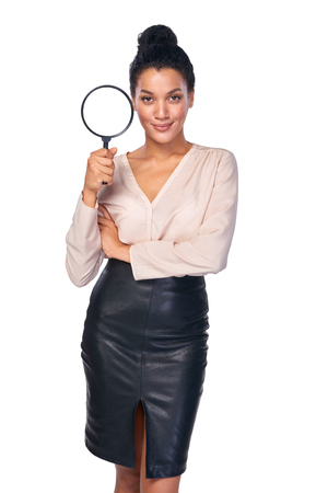 loupe: Search concept. Confident business woman standing holding magnifying glass, isolated over white