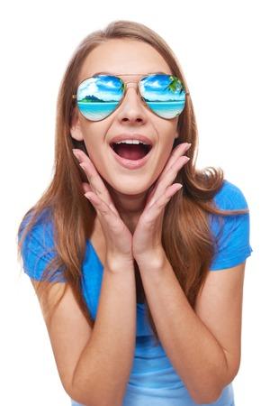 Vacaciones, viajes, concepto de vacaciones. Mujer sorprendida en gafas de sol con complejo de playa tropical de la reflexión con las manos en las mejillas