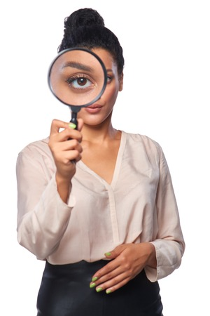 Search concept. Serious business woman standing looking at the camera through magnifying glass, isolated over white Zdjęcie Seryjne