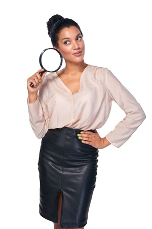 magnifying glass: Search concept. Confident business woman standing holding magnifying glass, isolated over white