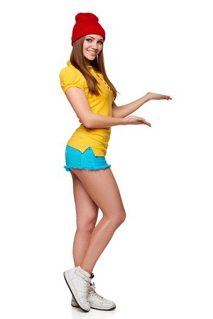 welcoming: Portrait of happy teen funky girl gesturing thumb up sign and showing open hand palm with copy space for product or text, over white background