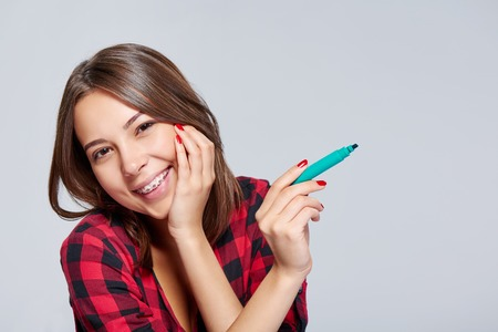 Closeup of happy smiling woman with a pen pointing at blank copy space, over grey background