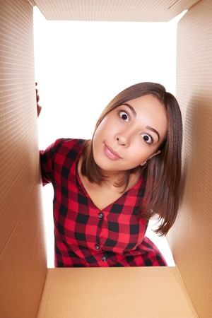 eyes opened: Delivery, relocation and unpacking concept. Surprised young female opening a carton box and looking peering inside with widely opened eyes Stock Photo