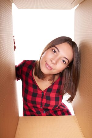 unpacking: Delivery, relocation and unpacking concept. Lovely young girl looking inside a carton box