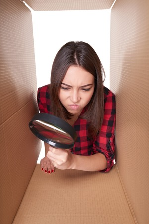 looking through: Young female peeking into carton box looking through magnifying glass with suspicion