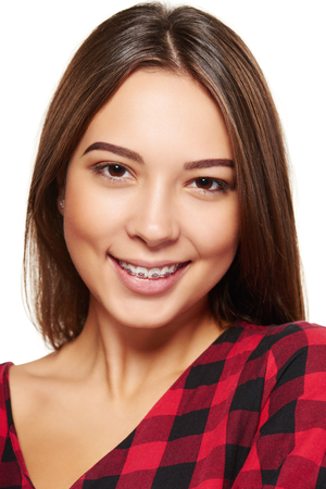 Closeup portrait of young teen female smiling with braces on her teeth