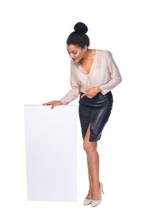 presenting: Business woman standing with blank white banner in full length presenting advertising your product, pointing at blank copy space, over white background Stock Photo