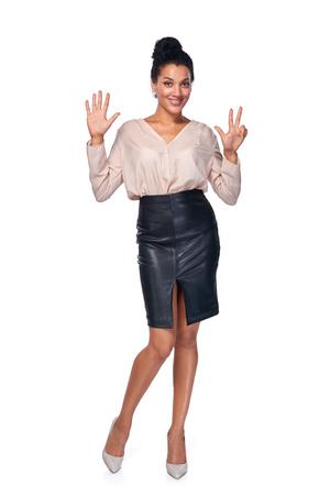 cuerpo femenino: Cuenta de la mano - ocho dedos. mestiza African American feliz - mujer caucásica que muestra ocho dedos standng en toda su longitud sobre fondo blanco Foto de archivo