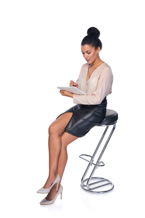 making notes: Full length mixed race african american - caucasian business woman sitting on the chair and making notes in a book Stock Photo