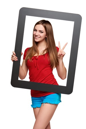 looking through frame: Beautiful bright girl standing looking through the frame and gesturing V sign, over white background