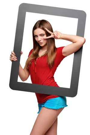 looking through frame: Beautiful bright girl standing looking through the frame and looking through hand V sign, over white background Stock Photo