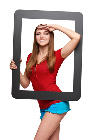 looking through frame: Beautiful bright girl standing looking through the frame and looking forward with palm on forehead, over white background Stock Photo