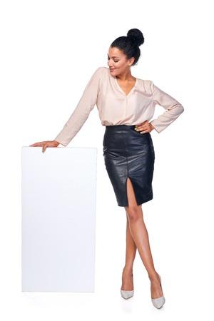 Sonriente mujer de negocios de pie apoyándose en la bandera blanca en blanco en toda su longitud, sobre fondo blanco Foto de archivo