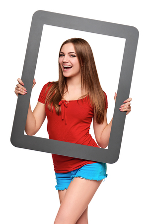 looking through: Beautiful bright girl standing looking through the frame, over white background Stock Photo