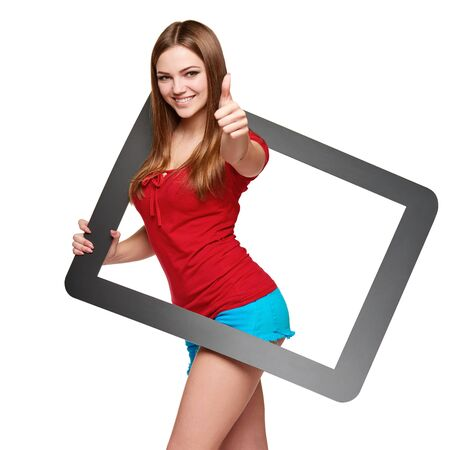 looking through frame: Beautiful bright girl standing looking through the frame and gesturing thumb up, over white background