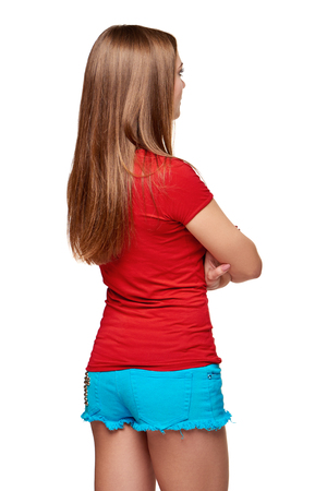 Back view of young female looking at blank copy space with folded hands, over white background