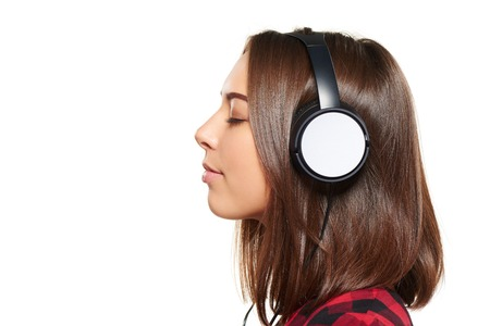 music listening: Side view closeup portrait of young female listening enjoying music in headphones with closed eyes, over white background