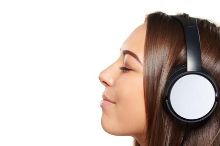 ojos cerrados: Vista lateral retrato de detalle de la escucha de mujer joven disfrutar de la m�sica en los auriculares con los ojos cerrados, sobre fondo blanco