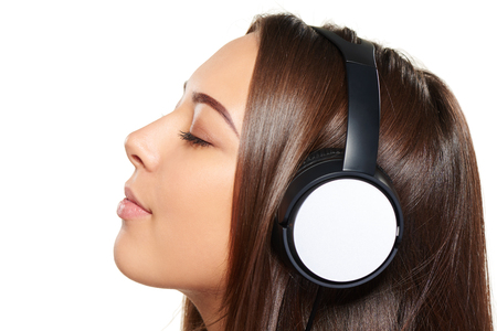 PRETTY WOMEN: Side view closeup portrait of young female listening enjoying music in headphones with closed eyes, over white background