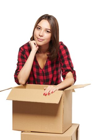 single dwelling: Smiling young woman leaning at opened cardboard box isolated on white background