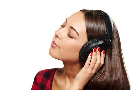 ojos cerrados: Retrato del primer de j�venes escuchando disfrutar de la m�sica en los auriculares con los ojos cerrados, sobre fondo blanco Foto de archivo