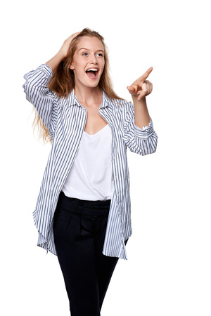 laugher: Happy excited woman pointing to the side at blank copy space, over white background