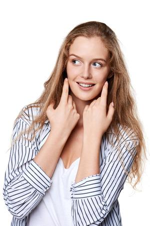 Retrato de la hermosa joven sonriente tocando la cara mirando hacia un lado en el espacio de la copia en blanco