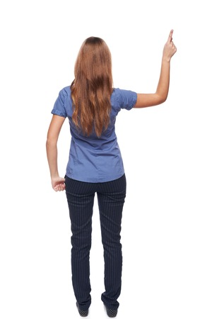 rear view: Back view of young casual female in full length pointing at blank copy space, isolated on white