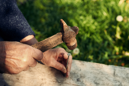 reconstruct: Closeup of mature man hands nails with old hammer an old weathered wooden plank outdoors against green grass background, cropped image Stock Photo