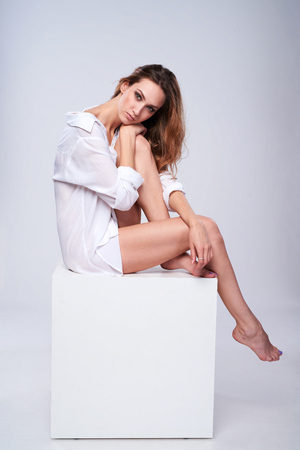 leggy girl: Full length beautiful leggy woman wearing boyfriend white shirt sitting on white box with blank empty copy space